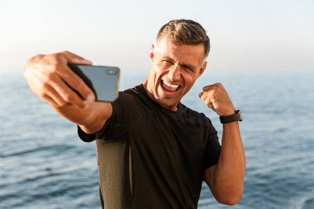 Foto de Cheerful handsome shirtless sportsman taking a selfie while standing at the beach and flexing biceps - Imagen libre de derechos