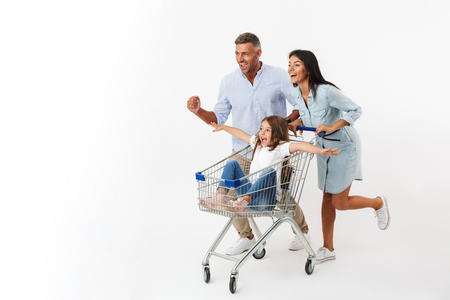 Foto de Happy family runnnig while shopping together with a supermarket trolley, little daughter sitting in a trolley isolated - Imagen libre de derechos