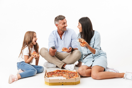 Portrait of a joyful family father, mother, little daughter having fun while eating pizza and watching TV isolated over gray background