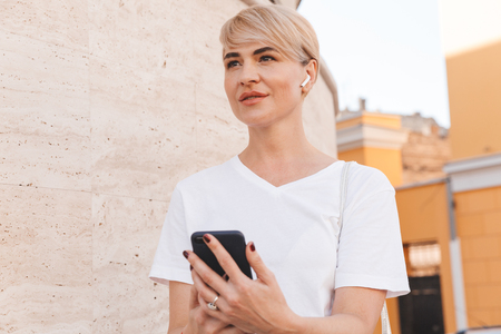 Foto de Photo of happy blond woman wearing white t-shirt and bluetooth earphone using mobile phone while walking in city street - Imagen libre de derechos