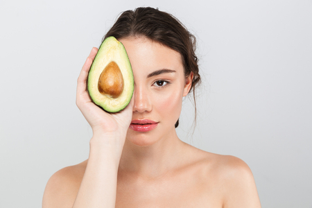Photo pour Beauty portrait of a lovely young topless woman with make-up holding sliced avocado isolated over gray background - image libre de droit