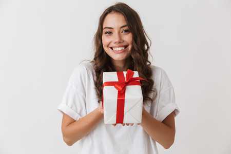 Photo pour Portrait of an excited young casual brunette woman holding present box isolated over white background - image libre de droit