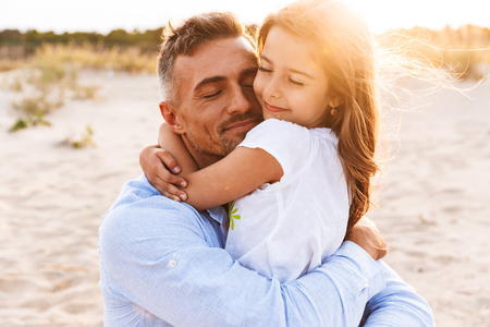 Photo for Happy father spending fun time with his little daughter at the beach, hugging - Royalty Free Image