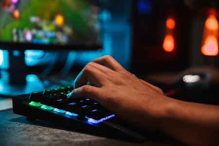 Hands of professional gamer man playing video games on computer in dark room using backlit colorful keyboard