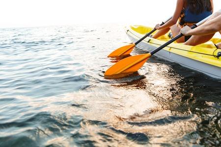 Foto de Cropped image of a young couple kayaking on lake together - Imagen libre de derechos