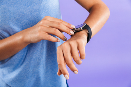 Close up of a young woman touching her smartwatch isolated over violet background