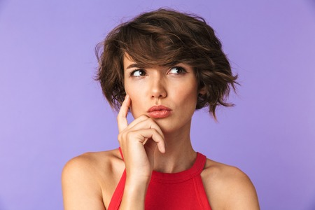 Close up portrait of a confused young girl thinking isolated violet background, looking away