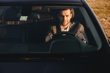 Foto de Front view of smiling bussinesman in suit driving his car - Imagen libre de derechos