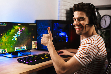 Photo for Portrait of joyful gamer guy in headphones playing video games on computer and showing thumb up - Royalty Free Image