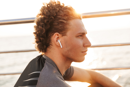 Photo pour Close up of a handsome young sports man listening to music with wireless earphones outdoors - image libre de droit