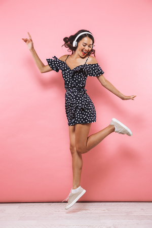 Photo pour Full length image of Cheerful brunette woman in dress and headphones listening music while jumping over pink background - image libre de droit