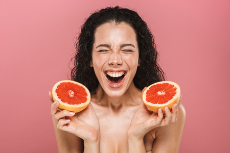 Photo for Happy photo of caucasian woman with long hair laughing and holding pieces of grapefruit isolated over pink background - Royalty Free Image