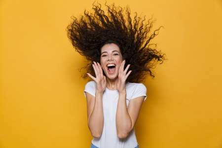 Photo of caucasian woman 20s laughing and having fun with shaking hair isolated over yellow background