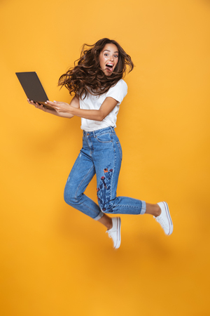 Foto per Full length portrait of a pretty girl with long dark hair jumping over yellow background, using laptop computer - Immagine Royalty Free