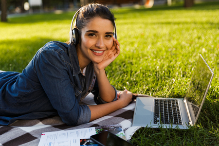 Foto de Image of amazing beautiful young woman student in the park using laptop computer listening music with headphones. - Imagen libre de derechos