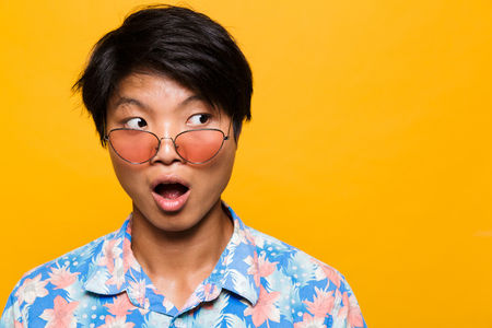Photo pour Close up portrait of a shocked asian man in sunglasses isolated over yellow background, looking away - image libre de droit
