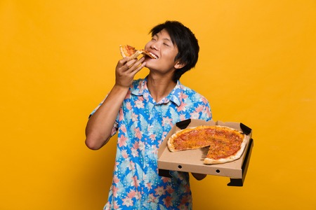 Photo pour Image of happy young asian man standing isolated over yellow background eat pizza. - image libre de droit