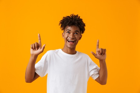 Foto de Cheerful young african man in t-shirt standing isolated over yellow background, pointing fingers up - Imagen libre de derechos