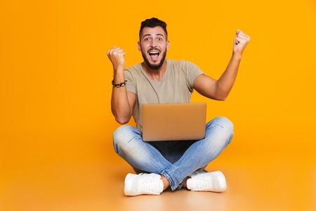 Photo pour Portrait of a happy young casual man sitting isolated over orange background, holding laptop computer on his lap, celebrating - image libre de droit