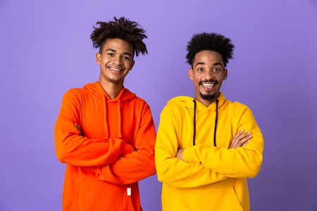 Photo pour Two happy african man friends dressed in colorful hoodies standing isolated over violet background, arms folded - image libre de droit