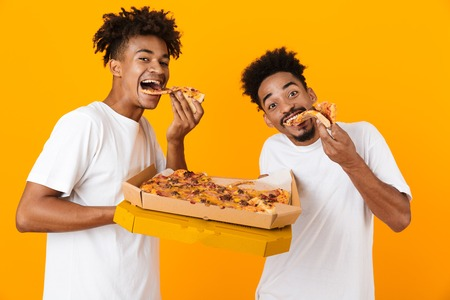 Photo pour Two joyful male african friends in t-shirts standing isolated over yellow background, eating tasty pizza from a box - image libre de droit
