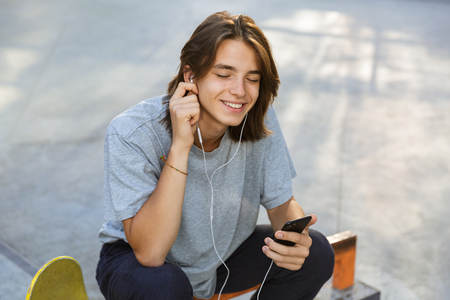 Foto de Joyful young guy spending time at the skate park, listening to music with earphones - Imagen libre de derechos