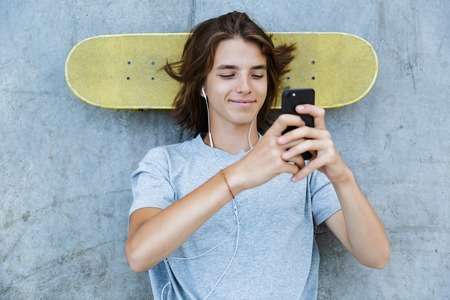 Photo pour Top view of a cheerful young teenge boy spending time at the skate park, laying on a skateboard at a ramp, listening to music with earphones - image libre de droit