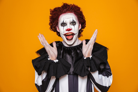Photo pour Funny man clown in costume looking camera with happiness isolated over orange - image libre de droit