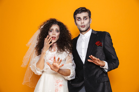 Foto de Photo of terrifying zombie couple bridegroom and bride wearing wedding outfit and halloween makeup scaring you isolated over yellow background - Imagen libre de derechos