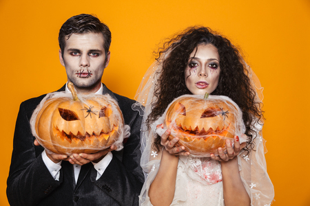 Photo of scary zombie couple bridegroom and bride wearing outfit and halloween makeup holding carved pumpkin isolated over yellow background
