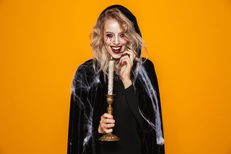 Photo for Tricky happy woman witch in black looking camera and holding candle isolated over orange - Royalty Free Image