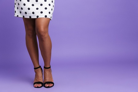 Foto de Close up of a woman in dress with long legs and high heels isolated over violet background - Imagen libre de derechos