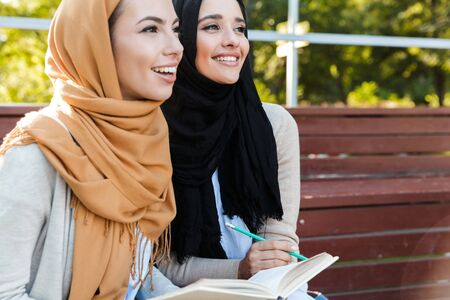Photo for Photo of religious islamic girls wearing head scarfs sitting in green park and reading book - Royalty Free Image
