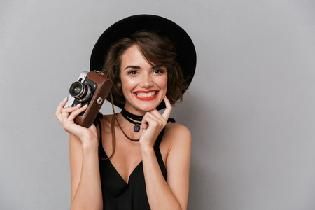 Photo of beautiful woman 20s wearing black dress and hat holding retro camera isolated over gray background