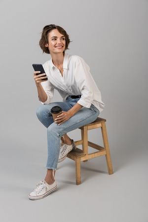 Photo pour Image of young business woman posing isolated over grey wall background sitting on stool using laptop computer chatting by phone. - image libre de droit