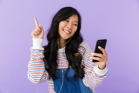 Photo pour Portrait of a happy young asian woman isolated over violet background listening to music with earphones, holding mobile phone - image libre de droit