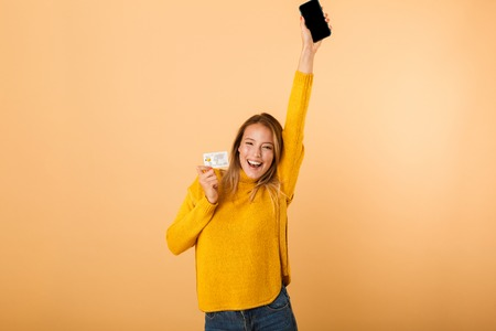 Foto de Portrait of a smiling young woman dressed in sweater standing isolated over yellow background, showing credit card, using mobile phone, celebrating - Imagen libre de derechos