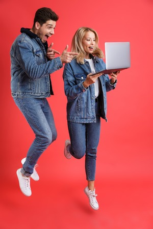 Full length portrait of an excited young couple dressed in denim jackets jumping together isolated over red background, looking at laptop computer, pointing finger