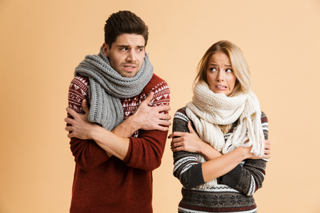 Photo pour Portrait of a frozen young couple dressed in sweaters and scarves standing together isolated over beige background, shaking, looking at each other - image libre de droit