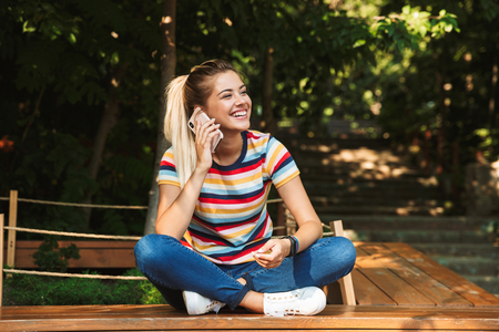 Photo pour Portrait of a smiling young teenage girl sitting on a bench at the park, talking on mobile phone - image libre de droit