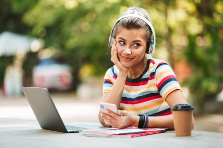 Photo for Portrait of a smiling young teenage girl sitting at the table at the park, listening to music with headphones, using mobile phone - Royalty Free Image