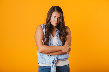 Foto de Upset young woman standing isolated over yellow background, holding arms folded - Imagen libre de derechos