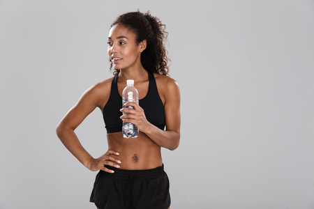 Foto de Portrait of a smiling young african sportswoman resting after training isolated over grey background, holding bottle with water - Imagen libre de derechos