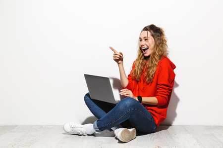 Foto de Portrait of an excited young woman wearing hoodie sitting isolated over white background, using laptop computer, celebrating success - Imagen libre de derechos