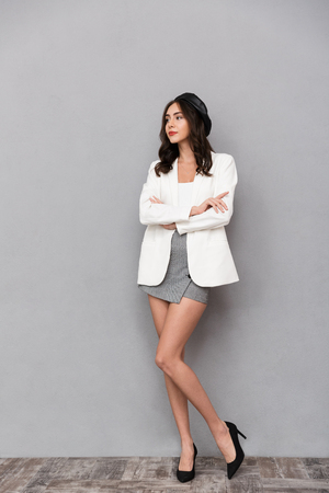 Foto de Full length portrait of a pretty young woman dressed in mini skirt and jacket standing over gray background, looking away - Imagen libre de derechos