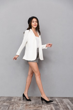 Photo pour Full length portrait of a pretty young woman dressed in mini skirt and jacket walking over gray background, looking at camera - image libre de droit