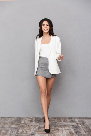 Foto de Full length portrait of a beautiful young woman dressed in mini skirt and jacket walking over gray background, looking at camera - Imagen libre de derechos