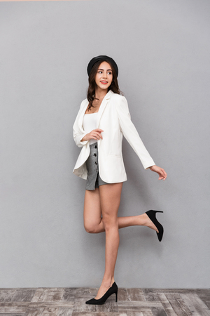Photo for Full length portrait of a pretty young woman dressed in mini skirt and jacket walking over gray background, looking away - Royalty Free Image