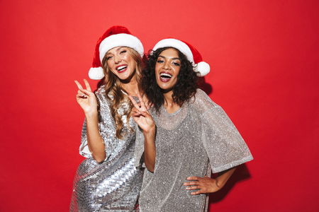 Photo pour Two cheerful young smartly dressed women celebrating New Year isolated over red background, posing - image libre de droit