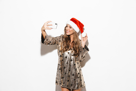 Photo pour Portrait of a pretty young woman wearing red hat celebrating New Year isolated over white background, taking a selfie with mobile phone - image libre de droit